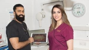 Arun & Nazia holding close up of patient teeth on ipad